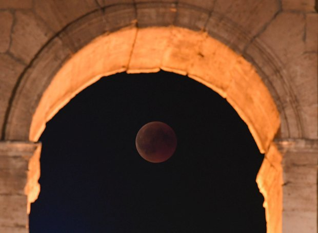ANCIENT: The red moon can be seen through an arch of the Colosseum in Rome